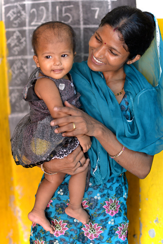 Mothers pick up their children from the Mobile Creches, Seemapuri Centre.<br /> <br /> Mobile Creches works with birth to 12 year old children living on the construction sites and slums of Delhi(NCR) since 1969. Integrated Daycare Centers for children on construction sites are run. Mobile Creches has so far reached out to 7,50,000 children, trained 6,500 women as childcare workers, run 650 daycare centres and partnered with 200 builders.<br /> <br /> Mobile Creches runs daycares centres where children are provided education, nutrition and healthcare. Community-women and NGOs are trained to provide care and speak-up for the child. The years of experience along with strong-networks helps in the advocay for policy-change.