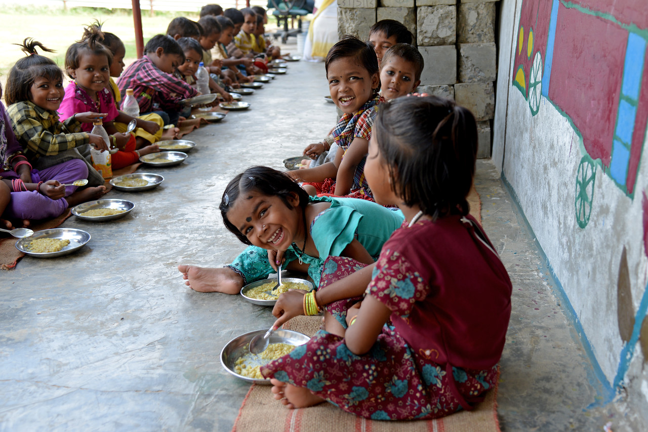 Riya (right), Payal and other children having a healthy meal at Mobile Creches, Vatika-83, Gurgaon, Delhi, NCR.<br /> <br /> <br /> <br /> Mobile Creches works with birth to 12 year old children living on the construction sites and slums of Delhi(NCR) since 1969. Integrated Daycare Centers for children on construction sites are run. Mobile Creches has so far reached out to 7,50,000 children, trained 6,500 women as childcare workers, run 650 daycare centres and partnered with 200 builders.<br /> <br /> Mobile Creches runs daycares centres where children are provided education, nutrition and healthcare. Community-women and NGOs are trained to provide care and speak-up for the child. The years of experience along with strong-networks helps in the advocacy for policy-change.