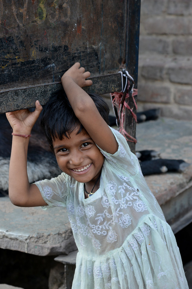 Child plays in the street while a community awareness meeting is being conducted by Mobile Creches in Seemapuri, Delhi.<br /> <br /> Mobile Creches works with birth to 12 year old children living on the construction sites and slums of Delhi(NCR) since 1969. Integrated Daycare Centers for children on construction sites are run. Mobile Creches has so far reached out to 7,50,000 children, trained 6,500 women as childcare workers, run 650 daycare centres and partnered with 200 builders.<br /> <br /> Mobile Creches runs daycares centres where children are provided education, nutrition and healthcare. Community-women and NGOs are trained to provide care and speak-up for the child. The years of experience along with strong-networks helps in the advocay for policy-change.