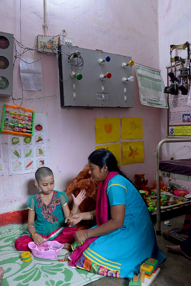 Nabisha, 9 years old, and her mother learn basic skills from the trainers. Children and their parents are trained in everyday activities, mobility, reading & writing by Nav Bharat Jagriti Kendra (NBJK) for deafblind children who have both hearing and visual disability. Different coloured lights & road signs on the wall and bells (sounds) are taught to aid everyday & independent activities.<br /> <br /> Nav Bharat Jagriti Kendra (NBJK) was established in 1971 by four engineering graduates who <br /> were sensitive to the causes of disparity, exploitation and poverty with an aim to <br /> establish a just society. Today they are the leading non-profit organization in Jharkhand <br /> running educational institution and health facilities.