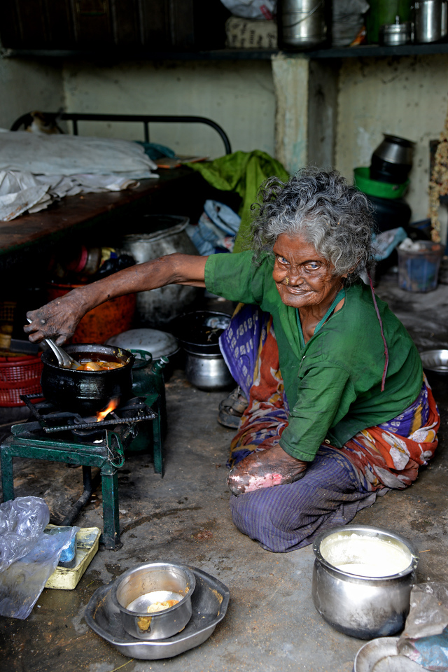 Old lady cooking in her small home in the community (colony).<br /> Rising Star Outreach of India, Kancheepuram District, Tamil Nadu, India