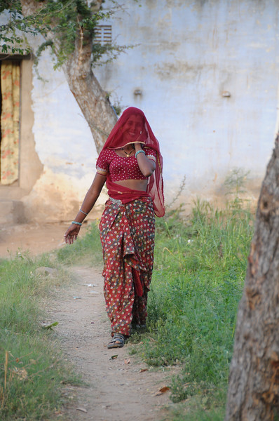 Mobile phone use in Rural Rajasthan (Village near Pushkar): Sayar Singh relative walking and talking while using the phone outside her house at Chamunda Matha Road, Pushkar, Rajasthan, India.