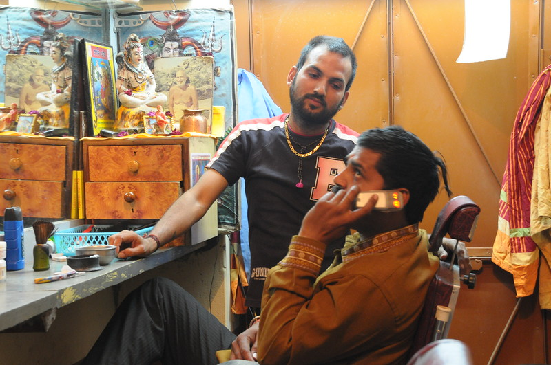 Mobile phone use in Pushkar: Important call. A hair cut put to hold to take a cellphone call in a barber's shop in Pushkar, Rajasthan, India.