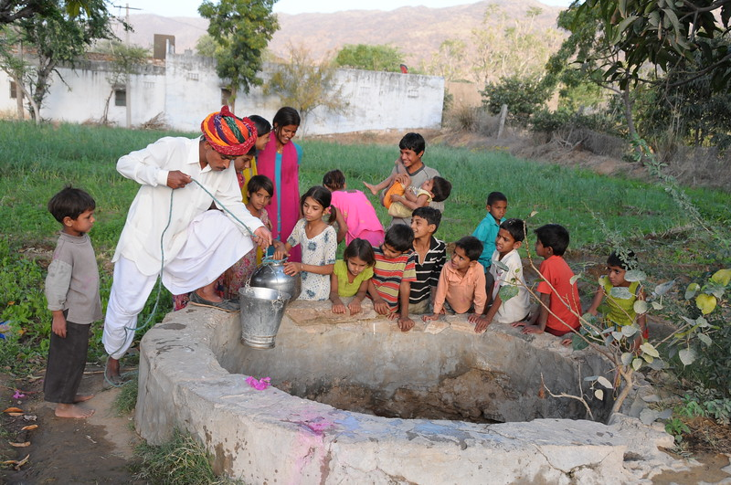 Mobile phone use in Rural Rajasthan (Village near Pushkar): Sayar Singh, Chamunda Matha Road, Pushkar, Rajasthan, India filling some water from the well.