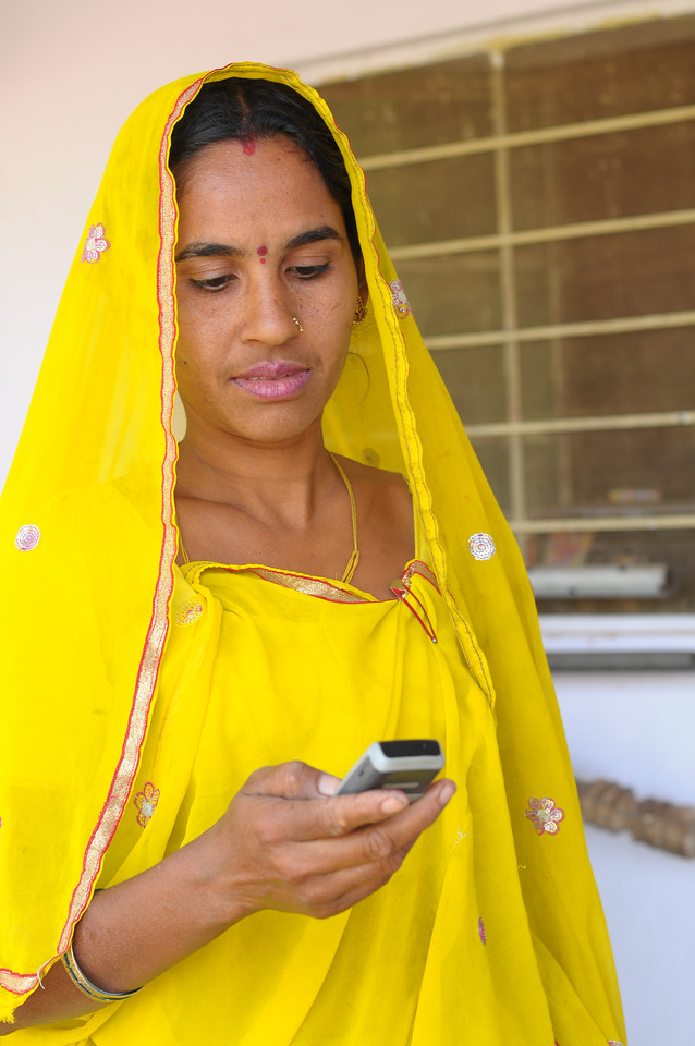 Mobile phone use in Rural Rajasthan (Village near Pushkar): Sayar Singh's wife calling on the mobile phone, Chamunda Matha Road, Pushkar, Rajasthan, India.