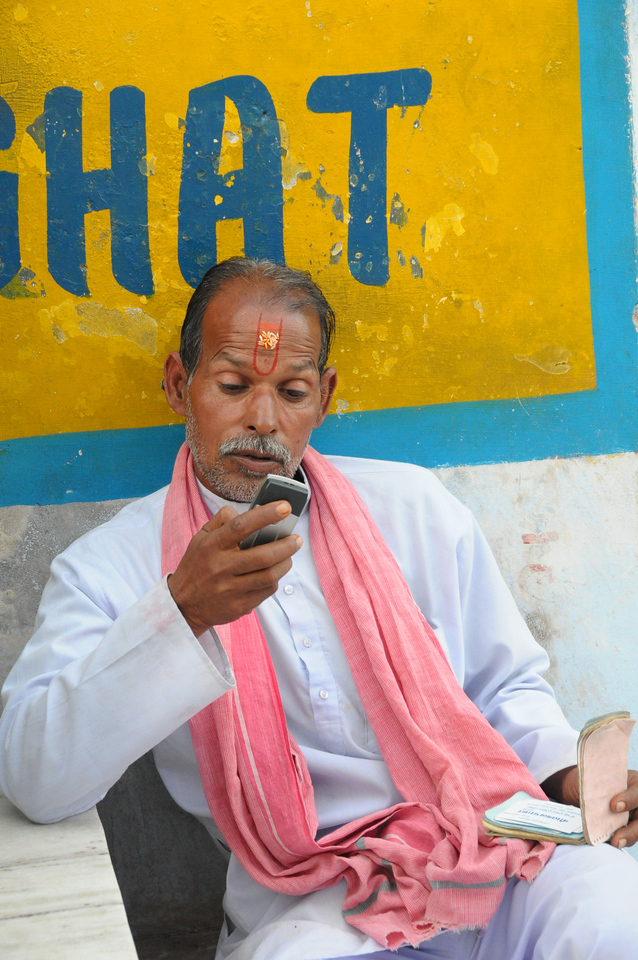 Mobile phone use in Pushkar: A local Pandit at the Ghat using a mobile phone to communication. Pushkar, Rajasthan, India.