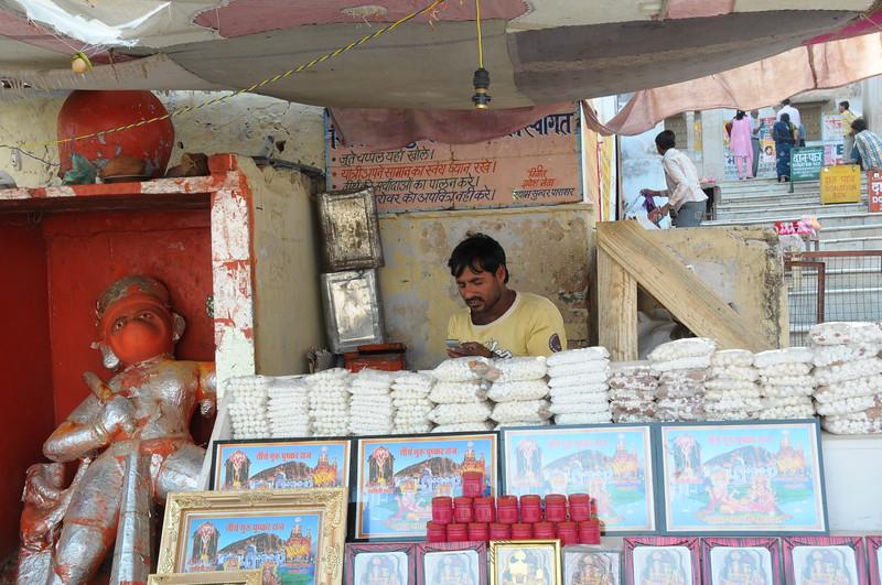 Mobile phone use in Pushkar: A puja item seller in Pushkar, Rajasthan, India.