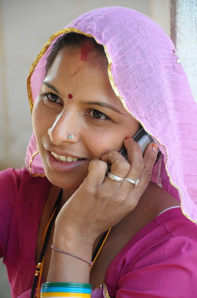 Mobile phone use in Rural Rajasthan (Village near Pushkar): Sister of Sayar Singh using the mobile phone.<br /> Sayar Singh, Chamunda Matha Road, Pushkar, Rajasthan, India.