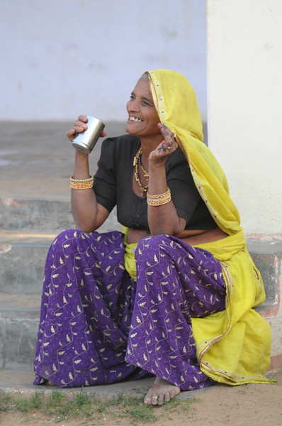 Mobile phone use in Rural Rajasthan (Village near Pushkar): Mother of Sayar Singh having a cup of tea, Chamunda Matha Road, Pushkar, Rajasthan, India.