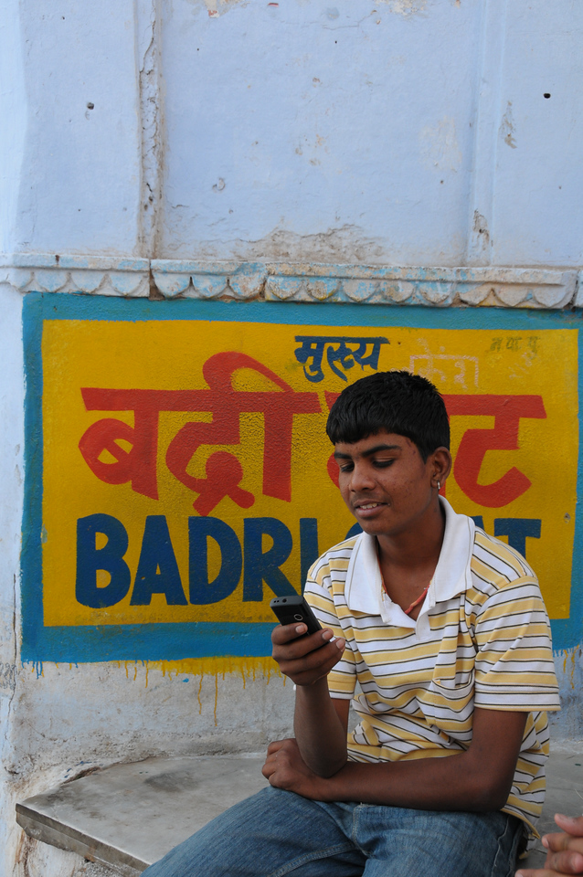 Mobile phone use in Pushkar: Little boy using a cellphone at Badri Ghat in Pushkar, Rajasthan, India.