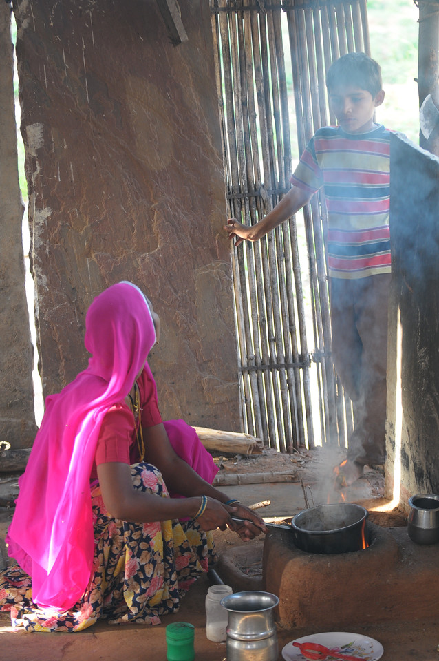 Mobile phone use in Rural Rajasthan (Village near Pushkar): Sayar Singh's wife making some tea at their home in Chamunda Matha Road, Pushkar, Rajasthan, India.