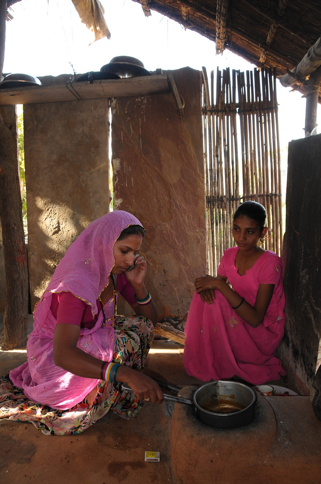 Mobile phone use in Rural Rajasthan (Village near Pushkar): Sister of Sayar Singh doing this house hold work and talking on the mobile phone.<br /> Sayar Singh, Chamunda Matha Road, Pushkar, Rajasthan, India.