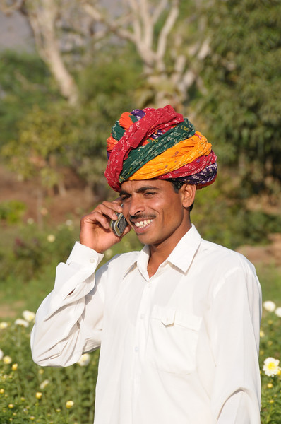 Mobile phone use in Rural Rajasthan (Village near Pushkar): Sayar Singh who stays Chamunda Matha Road, Pushkar, Rajasthan, India using his handphone to call the market for prices of his flowers.