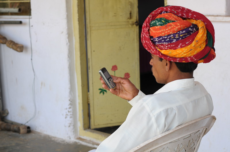 Mobile phone use in Rural Rajasthan (Village near Pushkar): Sayar Singh using his phone at his home at Chamunda Matha Road, Pushkar, Rajasthan, India.