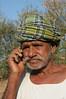 Mobile phone use in Rural Rajasthan (Village near Pushkar): Father of Sayar Singh talking on the mobile phone to keep in contact.<br /> Sayar Singh, Chamunda Matha Road, Pushkar, Rajasthan, India.