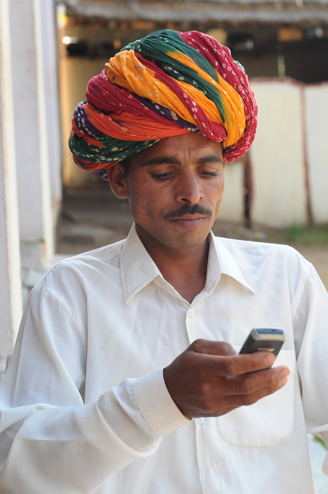 Mobile phone use in Rural Rajasthan (Village near Pushkar): Sayar Singh using his phone at his home at Chamunda Matha Road, Pushkar, Rajasthan, India.