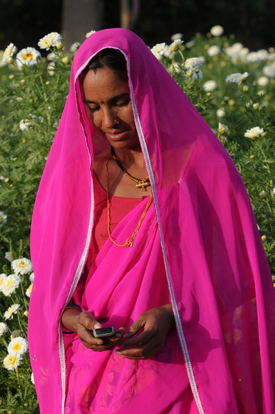 Mobile phone use in Rural Rajasthan (Village near Pushkar): Sayar Singh's wife using the mobile phone to keep in touch from their home at Chamunda Matha Road, Pushkar, Rajasthan, India.