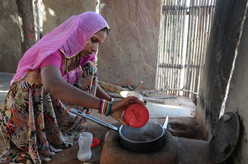 Mobile phone use in Rural Rajasthan (Village near Pushkar): Sister of Sayar Singh doing this house hold work.<br /> Sayar Singh, Chamunda Matha Road, Pushkar, Rajasthan, India.