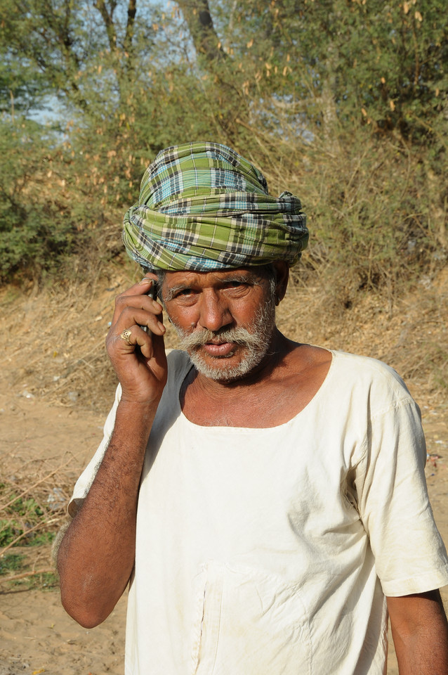 Mobile phone use in Rural Rajasthan (Village near Pushkar): Father of Sayar Singh talking on the mobile phone to keep in contact.<br /> Sayar Singh, Chamunda Matha Road, Pushkar, Rajasthan, India.