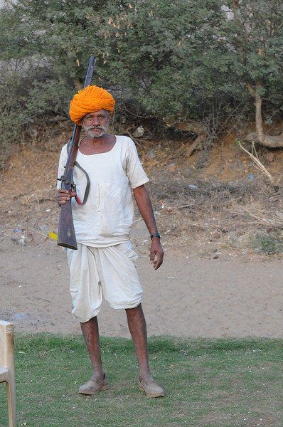 Mobile phone use in Rural Rajasthan (Village near Pushkar): Sayar Singh's father with his licensed rifle, Chamunda Matha Road, Pushkar, Rajasthan, India which is used to scare away animals from the field.