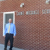 Nick Niemerg stands in front of Saint Michael School in Sigel. Niemerg is starting his first year as principal of the school after serving for two years as assistant principal of Vandalia High School.