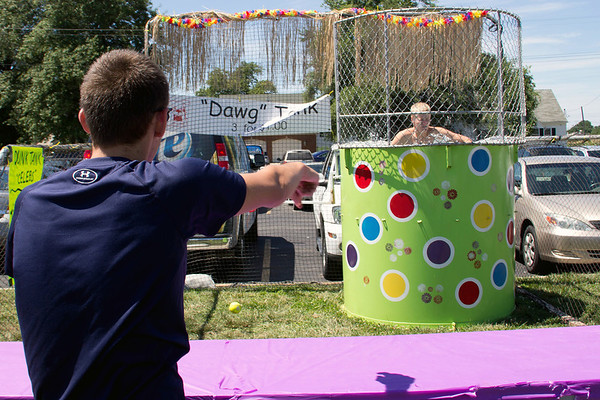 "Matt Gibson helps fellow St. Anthony High School student Nick Grunloh cool off by dunking him in the ""Dawg Tank"" at the St. Anthony parish picnic."