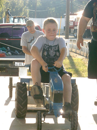 Iysten Syfert gives it his all during the pedal tractor competition Friday at the Cumberland County Fair in Greenup.