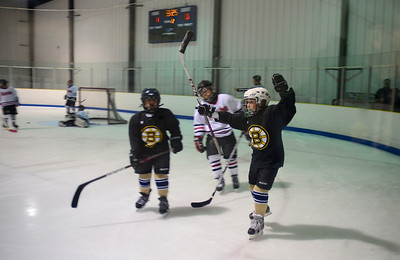 102812, Haverhill, MA -  A member of the Winthrop Squirt B youth hockey team - rebranded as mini Bruins - celebrates making the team's second goal against Watertown under the watchful eye of their temporary coach, Boston Bruins coach Claude Julien. Herald photo by Ryan Hutton