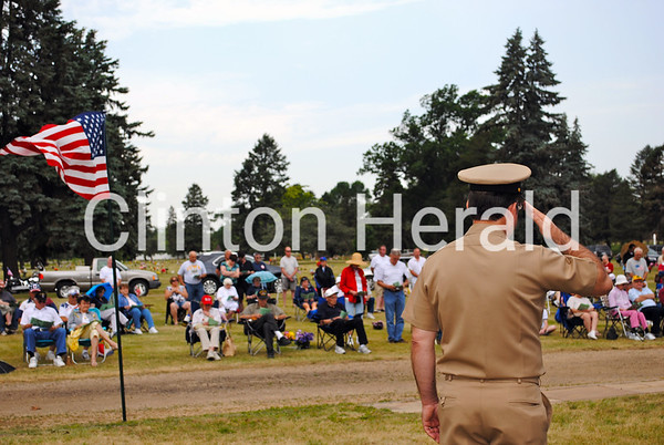 Retired Navy Veteran Tom Buelow salutes as the crowd listens to Eugene Steensen read the Honor Roll of 139 veterans at the Clinton Memorial Day Ceremony on May 28. • Katie Dahlstrom/Clinton Herald