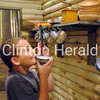 Aiden Estes, 8, plays with the utensils in the kitchen of the Sawmill Museum's new lumber camp exhibit on opening day. The kitchen is one of many child-sized buildings that allows kids to experience lumberjack life. - Katie Dahlstrom/Clinton Herald