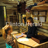 Sisters Abigail Linville, 8 (left) and Emma Linville, 10, play in the foreman's office/wanigan on Friday. The child-sized building is part of the Sawmill Museum's new lumber camp exhibit, which opened Friday. - Katie Dahlstrom/Clinton Herald