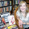Misty Fanderclai displays a few of her novels at the Schmaling Public Library in Fulton, Ill. - Natalie Conrad/Clinton Herald