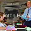 Clinton High School Science Department Chairman Wes Golden passes out information on Wednesday in his classroom to student Alyssa Kooi. Golden taught his last day Thursday before being deployed to Afghanistan with the Iowa Army National Guard. • Katie Dahlstrom/Clinton Herald