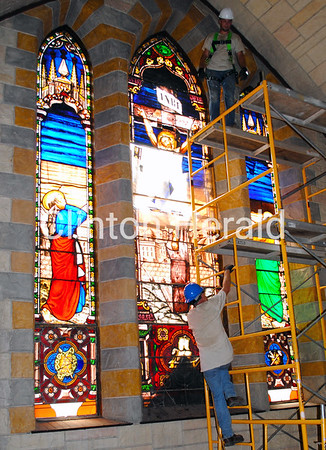 Stained-glass technician Shawn Bolt climbs scaffolding to help Glass Heritage co-owner Adrian English prepare to remove windows from St. Irenaeus on July 2. • Katie Dahlstrom/Clinton Herald
