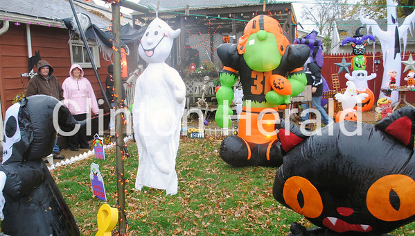 Spooky creatures greet passersby at the Fulton, Ill., home of Ray Blasdell and Julie Anderson, who are standing in the background at left. The couple assemble an elaborate display each Halloween and Christmas. - Natalie Conrad/Clinton Herald