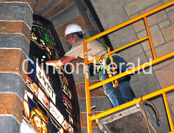 Glass Heritage co-owner Adrian English examines the stained-glass window at St. Irenaeus on July 2. • Katie Dahlstrom/Clinton Herald