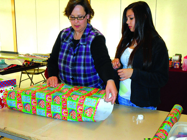 Michelle Brockett and Tara Torres, both of Watson, wrap gifts at Village Square Mall. Although they wrap gifts for free, donations are accepted to benefit their Relay for Life team.