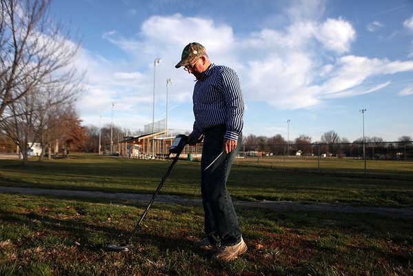 "Scott Lauwers, of Mattoon, uses a metal detector near the sidewalks at Evergreen Hollow Park in Effingham. Lauwers said he and his son were out searching for coins to make the best of the warm weather before they had to put their detectors away for the winter. ""It's just something to do,"" he said. ""It keeps you out of trouble."""