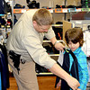Effingham County Deputy Sheriff Eric Higgs sizes up second-grader Alec Williams for one of his many gifts put on by Shop with a Deputy at Wal-Mart recently. Approximately 100 students shop with deputies every year.
