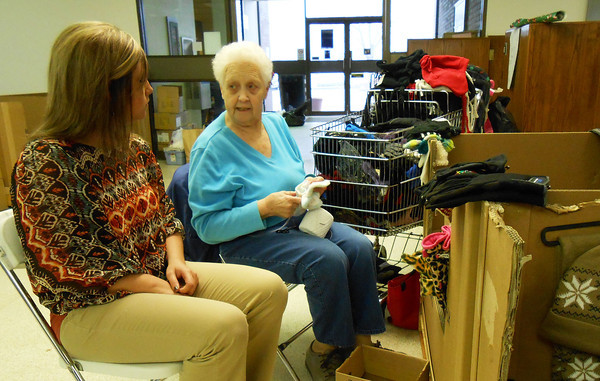 Shelby Beck, left, and Edie Allen visit while volunteering for the Christmas Store, which offers items to those less fortunate in the area. Allen sorts gloves now that she has trouble standing, while Beck is in charge of arranging new toys donated for the program.
