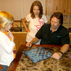 Olivia Rueter ponders her next move during a checkers game with dad Kevin, as mom Belinda looks on.