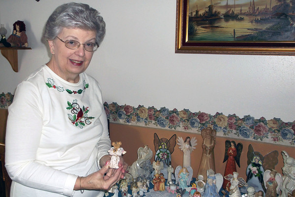 Carol Martin stands with an angel given to her when her mother passed away. Carol's mother gave her first angel, made of candle wax, in the 1950s. As of today, she has collected more than 100 angels that are displayed throughout her home.