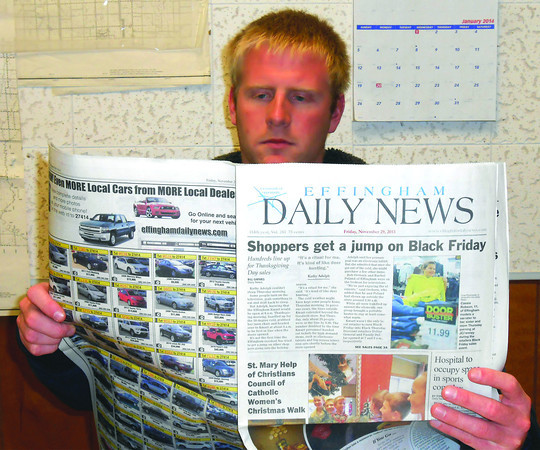 Matt Feldhake reads a copy of the Effingham Daily News, which he has delivered for 13 years. Feldhake believes delivering the paper taught him the value of staying active and working hard.