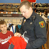 Officer Tom Webb keeps track of the shopping list for third-grader Braden Sweeney of Effingham during the Shop with a Cop event at Wal-Mart.