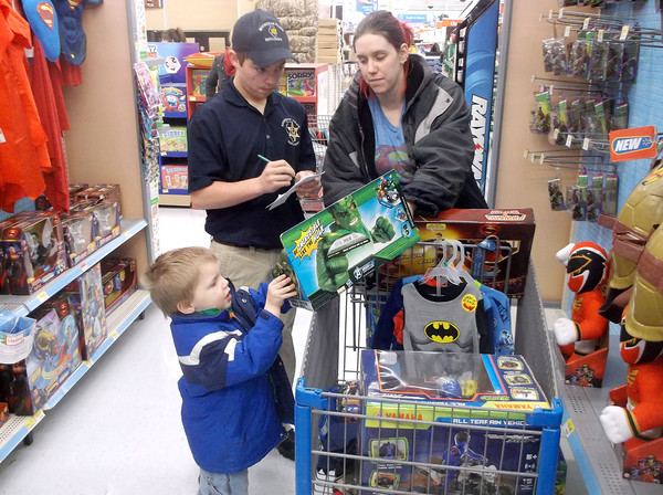 Effingham Explorer Post member Braden Harris, left, keeps track of the list for 3-year-old Ethan Sumner as mom Kerri Harris looks on in the toy aisle at Walmart during the annual Shop With a Cop event. The Harrises are not related.