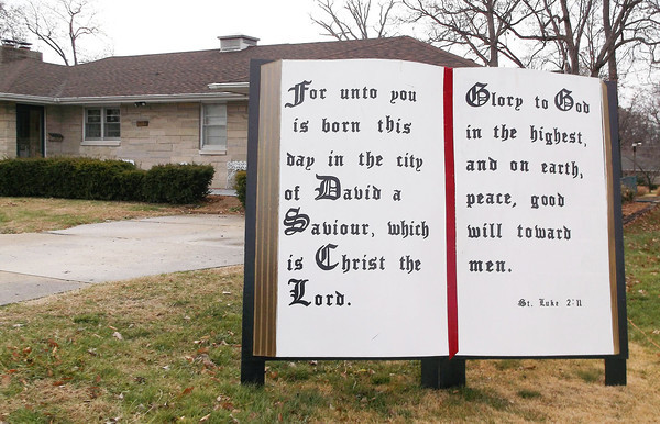 A large sign built to look like a Bible stands in the yard of Robert and Lisa Hayes' yard on Willow Street. Robert feels people need to remember religion during the holidays.