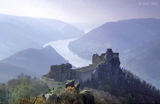 [AUSTRIA.NIEDER 03597] 'Ruins of Aggstein castle.'  In the Aggstein stronghold lived robber baron Scheck. If you didn't pay toll for passing the Danube at the foot of his eyrie, you had the choice between the eight meters deep Hungerloch (hunger pit) or a jump from his Rosengärtlein, a nicely smelling balcony with one of the most beautiful views of the Wachau. Today you can enjoy this romantic panorama with a little less stress.