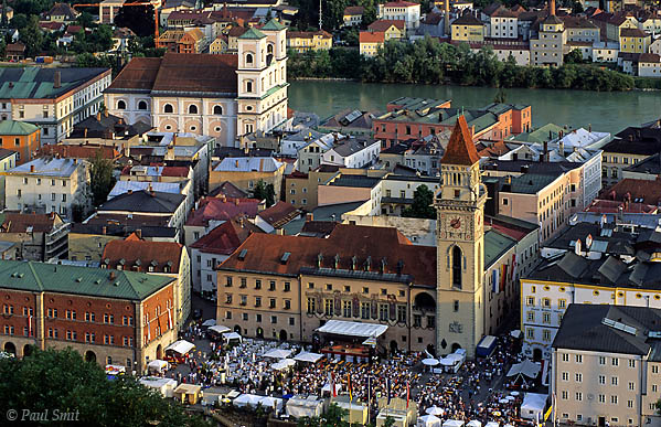 [GERMANY.BAYERN 00648] 'Party in Passau.'  Passau is having a party at the town hall square.  Passau is the last German town along the Danube before the Austrian border and maybe the prettiest. Here the Inn (in the background) flows into the Danube and the Ilz as well. You never need to search a long time to find a river front promenade. The Inn is green and the Ilz brown, so whatever people sing about the Danube, this never adds up to blue. Photo Paul Smit.