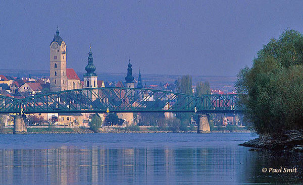 [AUSTRIA.NIEDER 03639] Danube with city Krems-und-Stein.'  Stein and its railway bridge over the Danube. Double town Krems-und-Stein is my favourite historical town along the Austrian Danube. With its new Kunstmeile, the Mile of Art connecting Krems with Stein, several museums line up, among them the Caricature Museum. Be drawn into a church by the sound of its organ, get lost in the cobbled streets or climb above the roofs on the vineyard slopes.