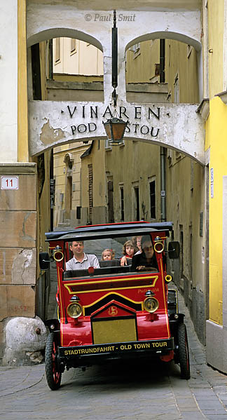 [SLOVAKIA.WEST 03553]  'Bratislava old town tour.'  Kitschy old town tour 'oldtimer' coming out of the narrowest alley of Bratislava, Bastová Ulica. Photo Paul Smit.